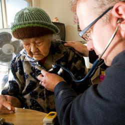 picture of a UW Medicine palliative care specialist checking a patient's breathing.
