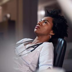 picture of African American female doctor sitting in a chair while working late