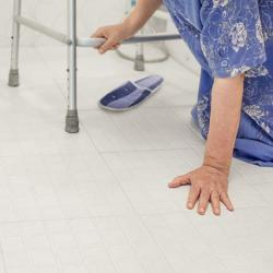 Older woman touching the ground and holding onto her walker.