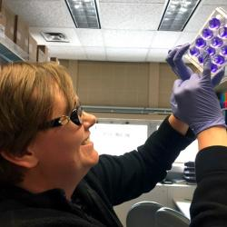 Dr. Susan Fink, a lab medicine specialist, displays containers used in a test of viral infection.