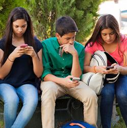 picture of four high schoolers on cell phones