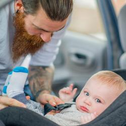 A parent buckles a child into a rear-facing safety seat.