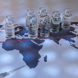 picture of COVID-19 vaccine vials atop a world map