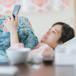 ill woman in bed looking at smartphone