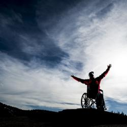 Man in a wheelchair at sunset
