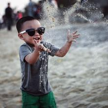 Child wearing sunglasses playing on the beach