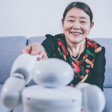 picture of senior citizen reaching out to touch robot