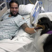 Patient Kepu Savou with therapy dog Mason