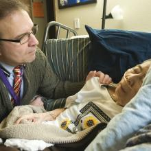 Darrell Owens,  nurse practitioner, outpatient palliative and supportive medicine services, during home visit to a patient receiving palliative care at end of life. The patient's son is present, as well.