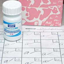 picture of aspirin bottle atop calendar