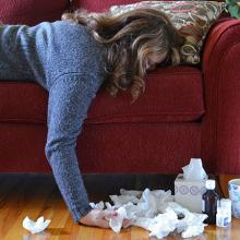 picture of sick woman lying face-down on sofa with tissues around