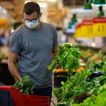 Man wearing mask shopping for groceries