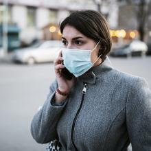 Woman wearing a mask talking on the phone