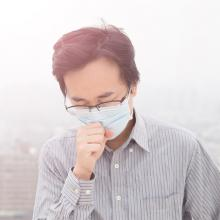 picture of person wearing breathing mask amid smoky air