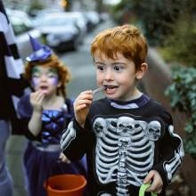 Child in Halloween costume eating candy