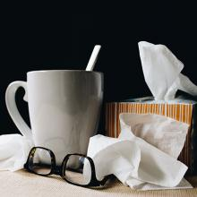 Tissues, cup, glasses on a nightstand