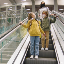 picture of mother and two daughters masked on mall escalator