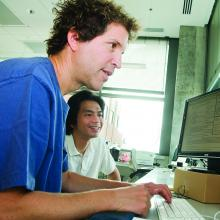 David Baker, Ph.D., professor of biochemistry, works with a colleague in his lab at the Institute for Protein Design.