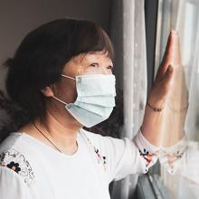 picture of older Asian woman looking outside through window
