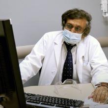 Dr. Ganesh Raghu looking at a computer screen