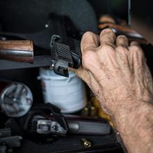 senior citizen reaching into a gun safe for a firearm