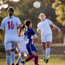 a teen soccer player heads the ball
