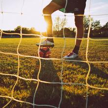 Man in cleats by soccer goal