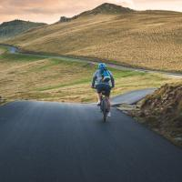 A bike rider enjoys a winding road and scenic countryside while his helmet reduces his risk of brain injury in the case of a fall or crash.